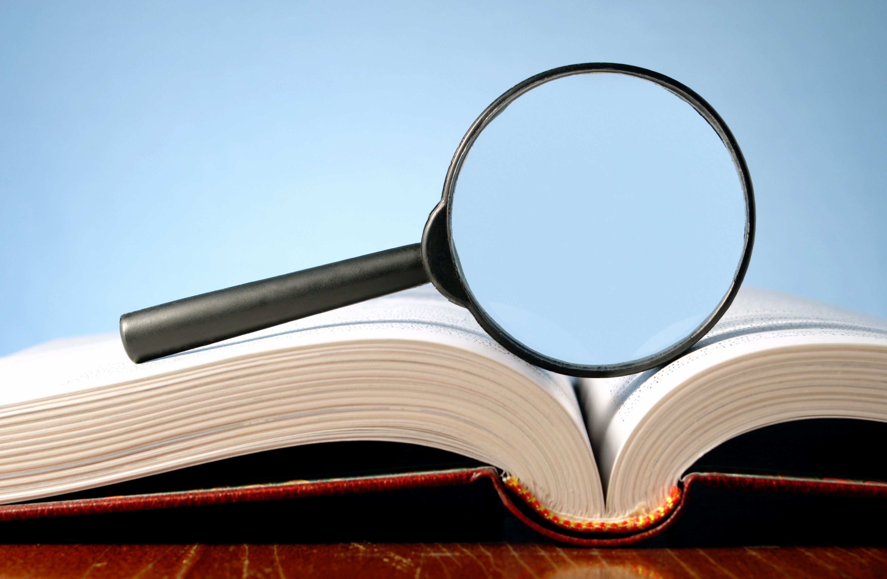 12247812 - magnifying glass and an open book on a table